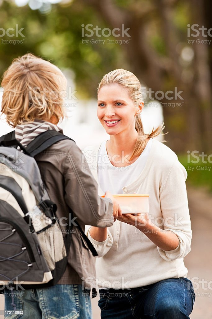 Mother giving her son a lunch box royalty-free stock photo