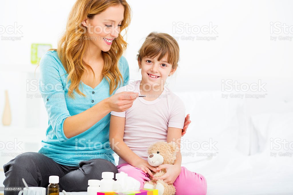 Mother Giving Liquid Medicine to Child. stock photo