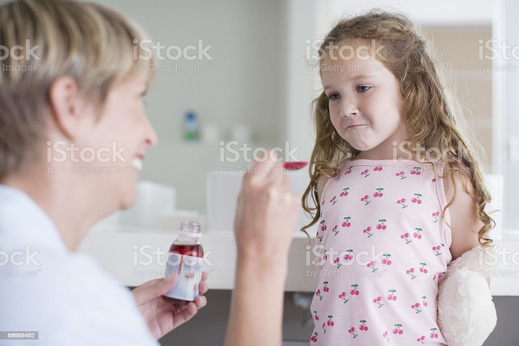 Mother giving medicine to stubborn doctor stock photo