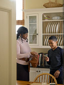 Mother giving son (12-13) pocket money in kitchen