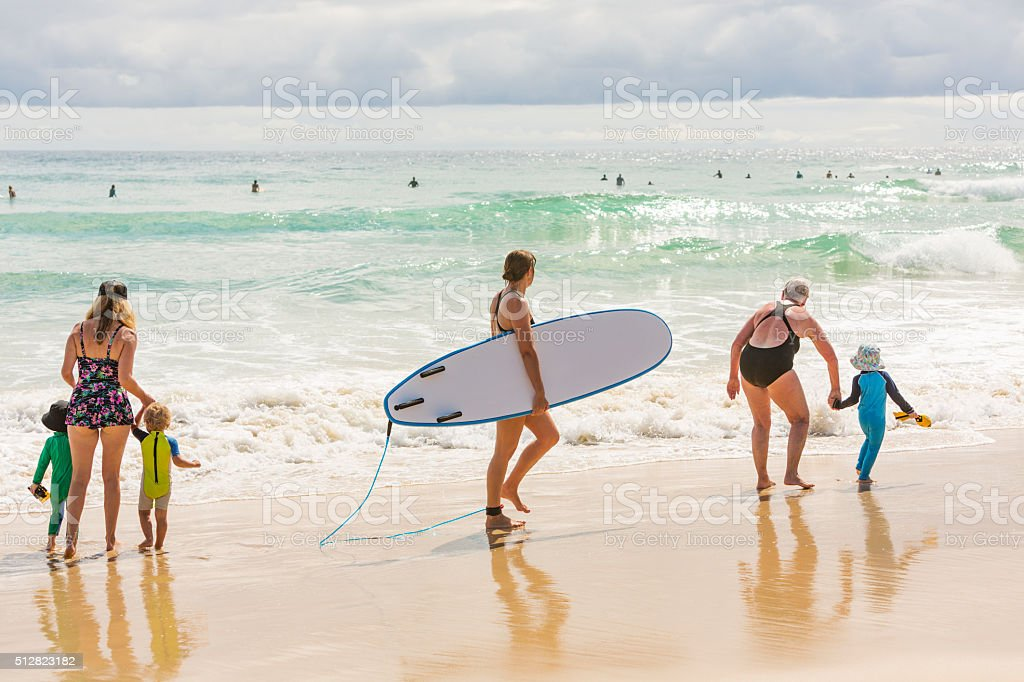 Mother, Grandmother and Children at the Beach With Female Surfer stock photo