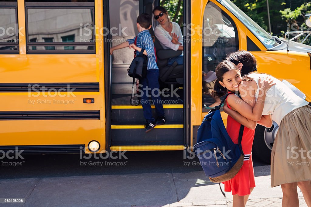 Mother greeting elementary age girl getting off school bus. stock photo