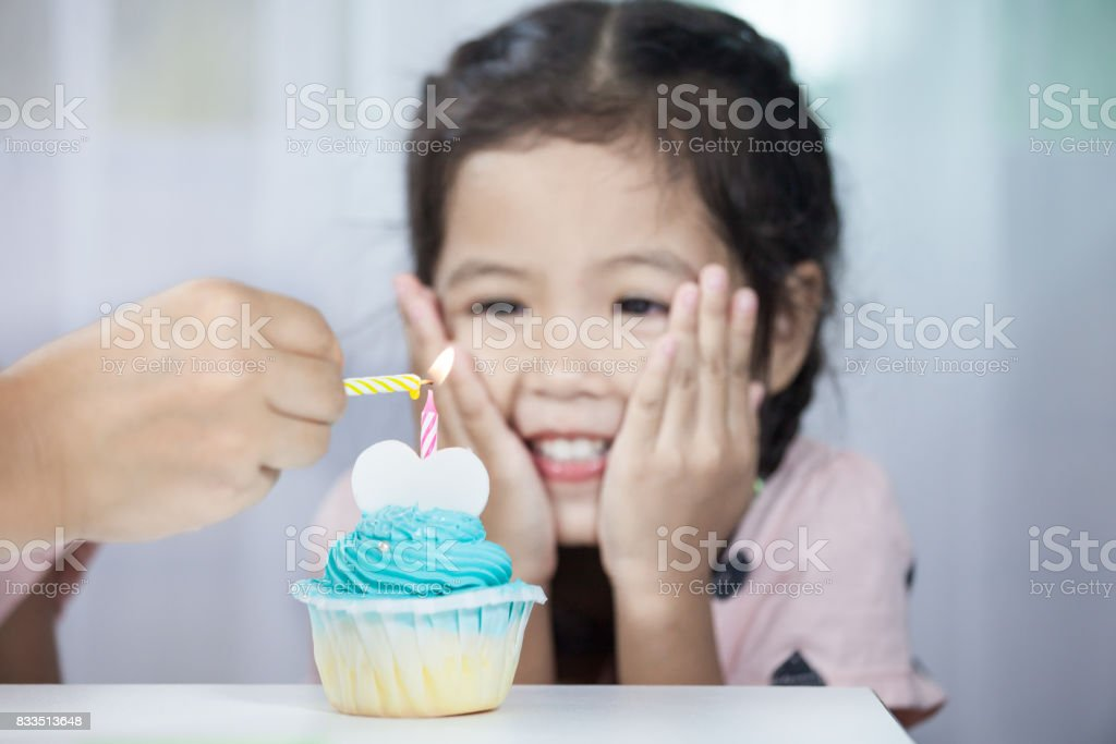 Mother hand lighting candle on birthday cupcake for child girl celebrating stock photo