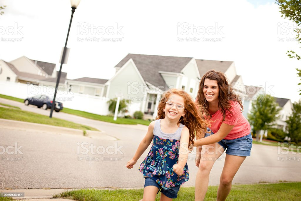 Mother Happily Chasing Her Daughter Outside on Summer Day stock photo