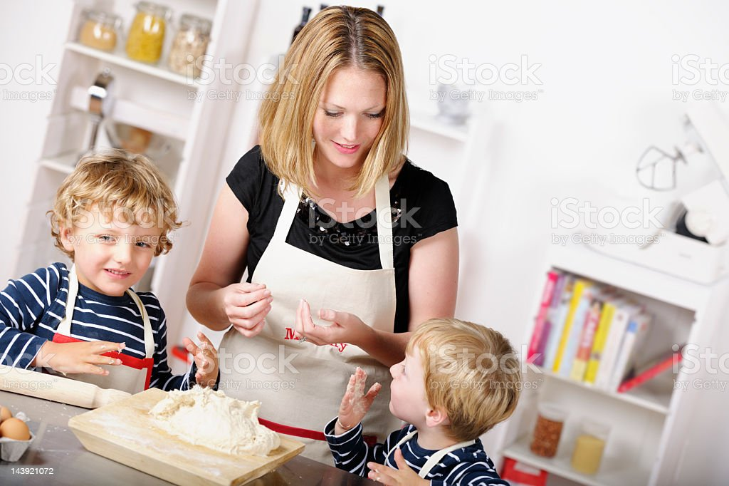 Mother Having Fun Day In The Kitchen With Her Sons stock photo