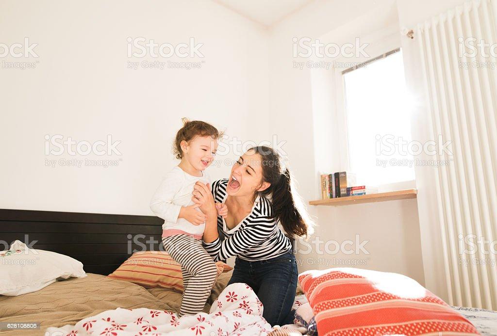 Mother having fun with her daughter in her bedroom stock photo