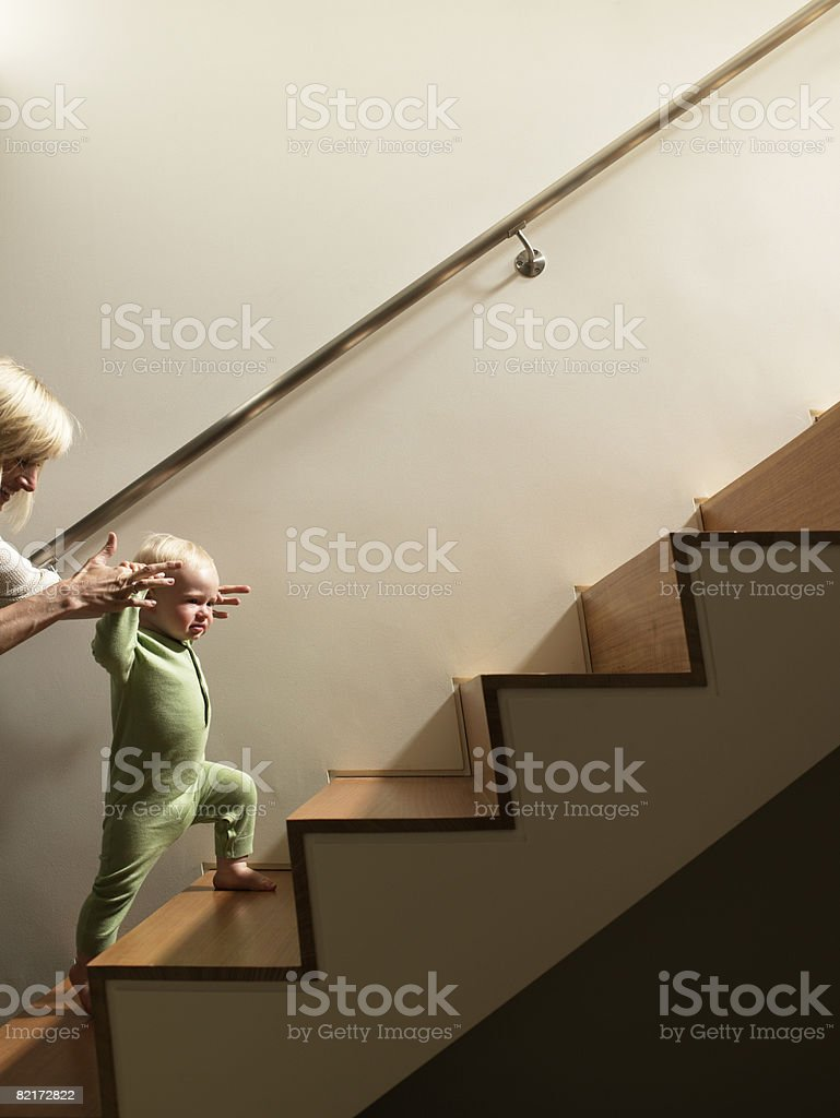Mother helping baby boy walk up stairs stock photo