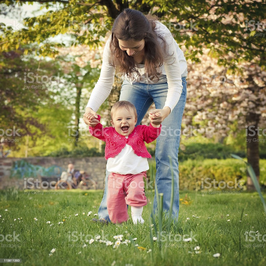 Mother helping baby outdoors take first steps stock photo