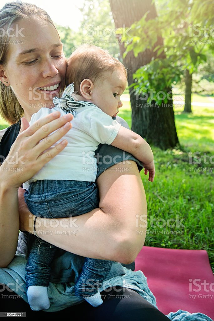 Mother helping baby to burp outdoors in summer. stock photo
