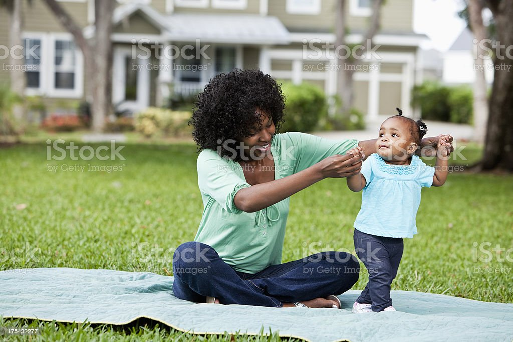 Mother helping baby walk stock photo