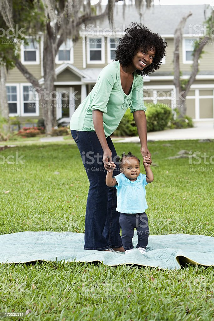 Mother helping baby walk royalty-free stock photo
