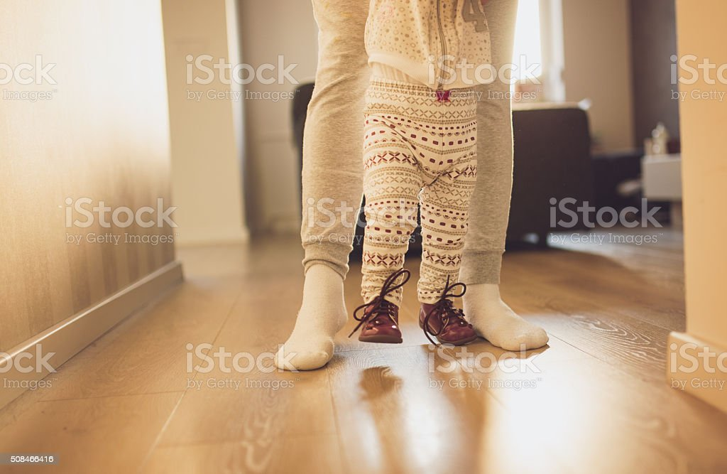 Mother helping cheerful baby learn to walk stock photo