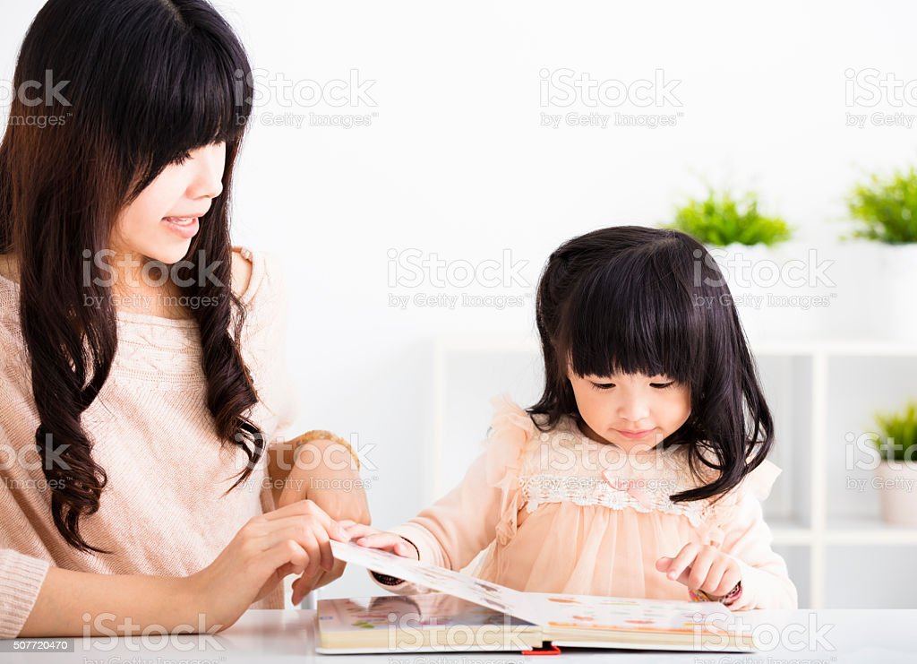Mother  helping child daughter to reading stock photo
