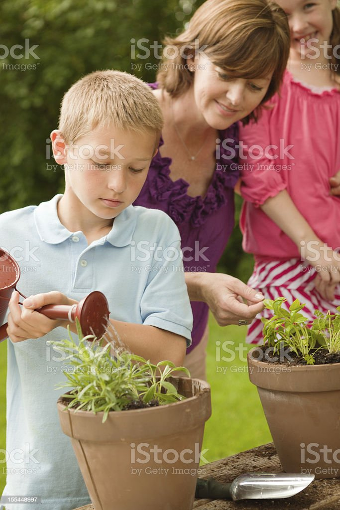 Mother Helping Children Gardening and Planting Flowers Hz royalty-free stock photo