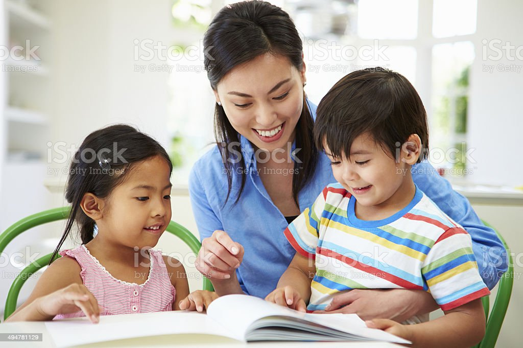 Mother Helping Children With Homework stock photo