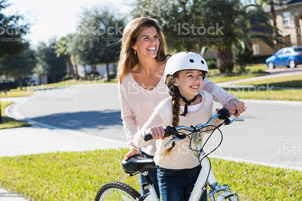 Mother helping daughter get on bicycle stock photo