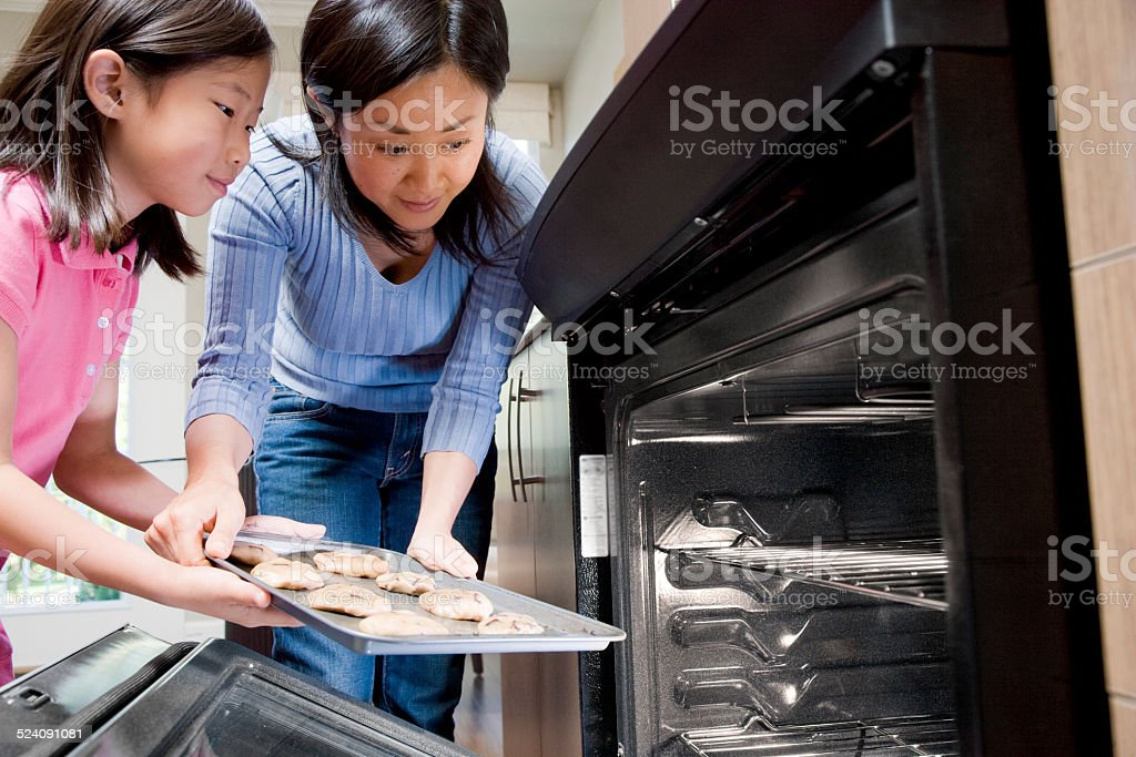 Mother Helping Daughter Put Cookies in Oven stock photo