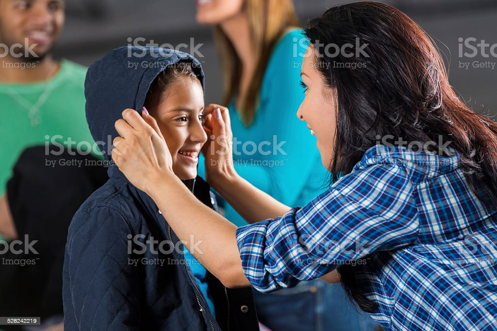 Mother helping daughter try on coat at donation drive stock photo