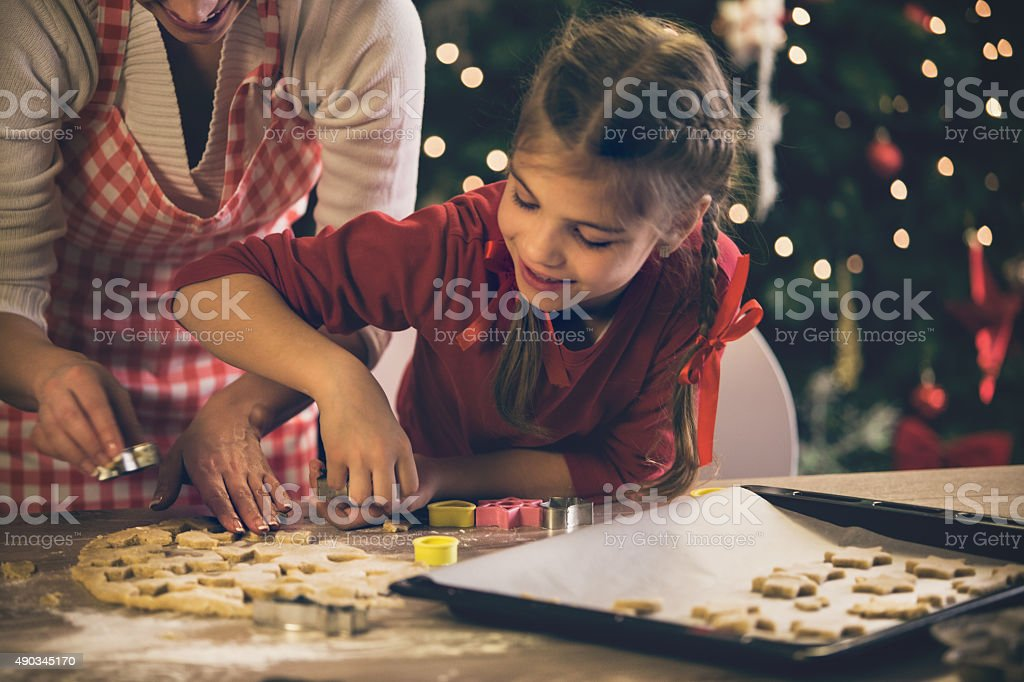 Mother helping daughter with christmas cookies stock photo