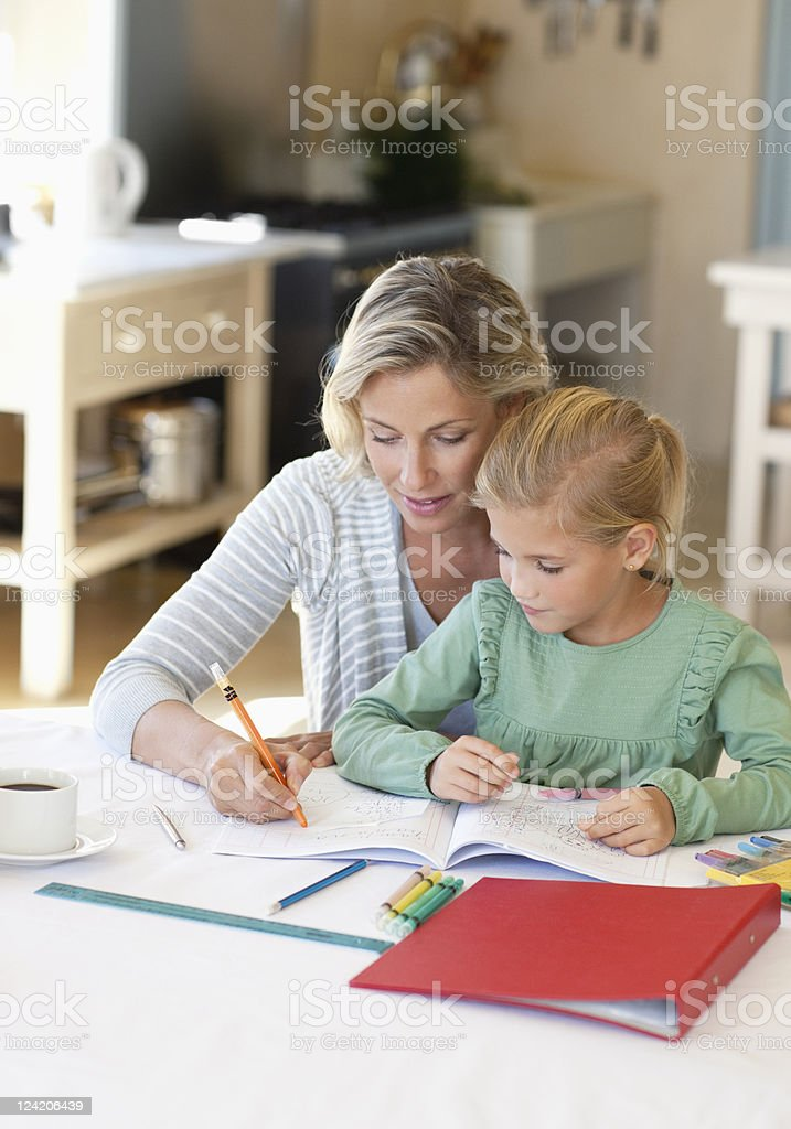 Mother helping daughter with her homework stock photo