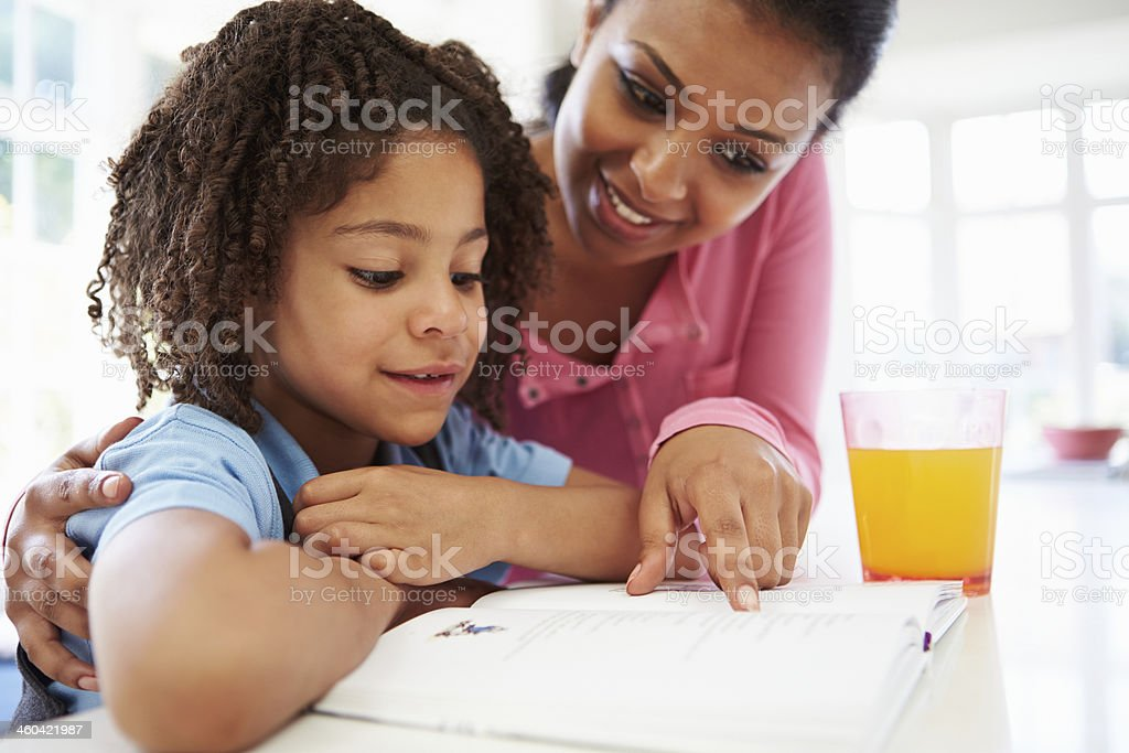 Mother Helping Daughter With Homework In Kitchen stock photo