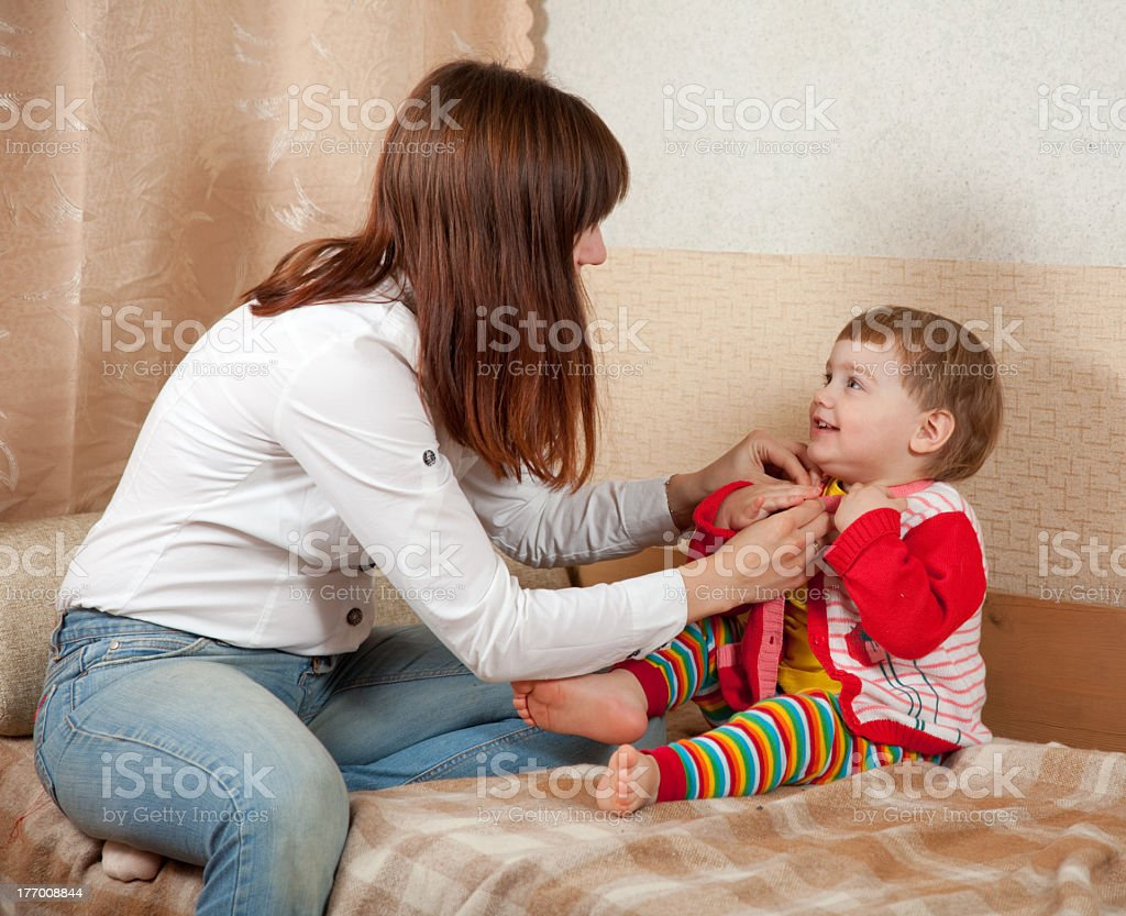 Mother helping her baby daughter to get dressed stock photo