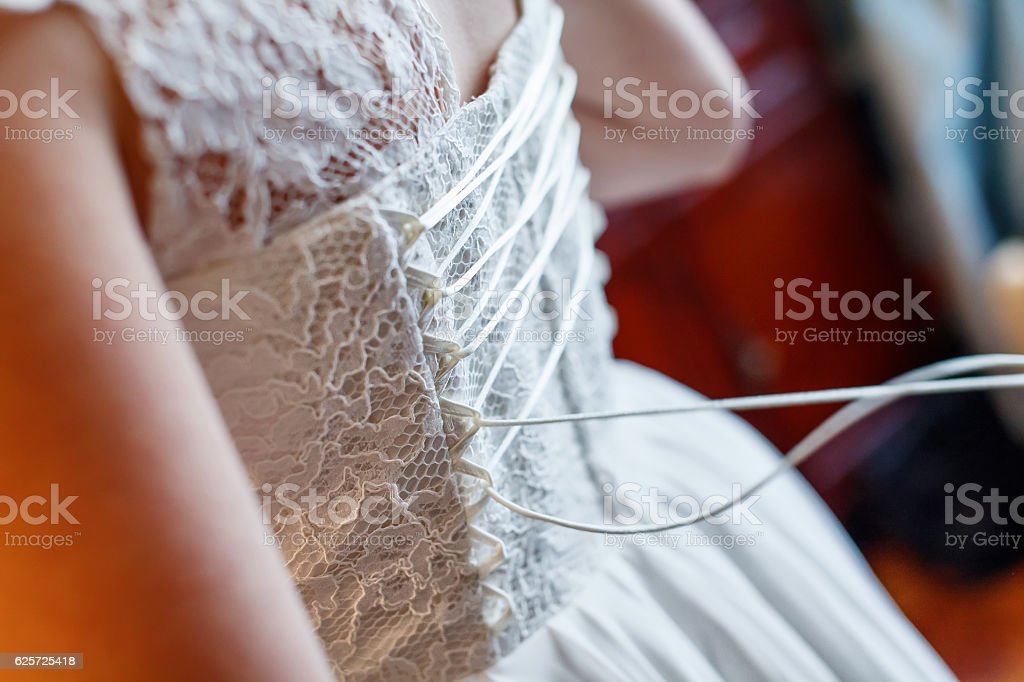 Mother helping her daughter get dressed for wedding. stock photo