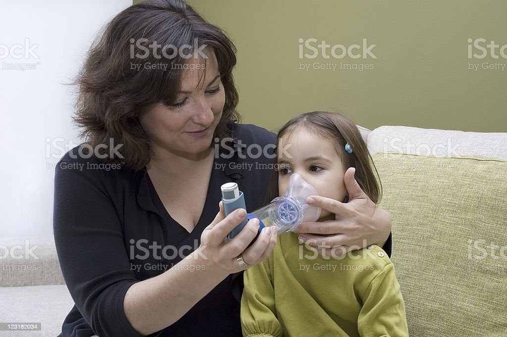 A mother helping her daughter use an inhaler stock photo