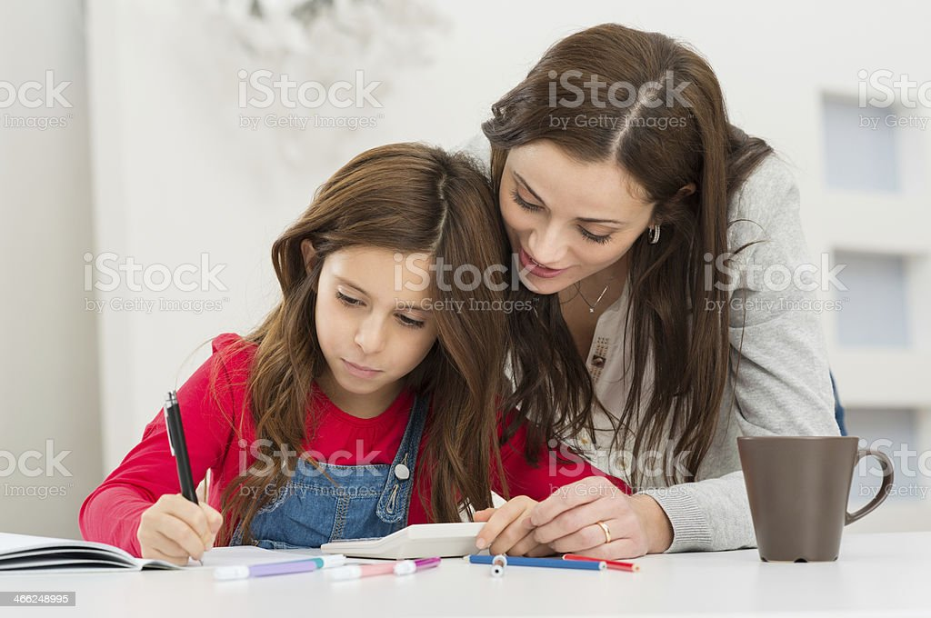 Mother Helping Her Daughter While Studying stock photo