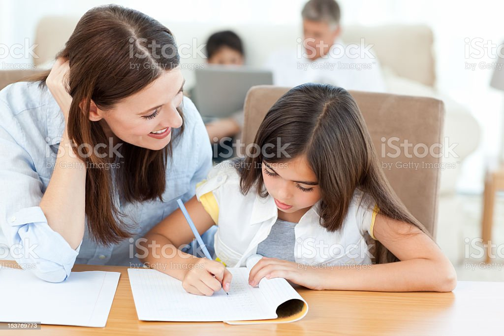A mother helping her daughter with homework  royalty-free stock photo