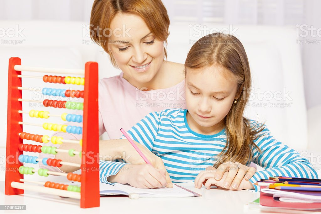 Mother helping her daughter with math royalty-free stock photo