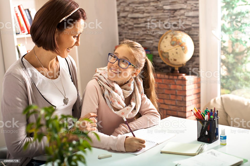Mother helping her daughter with studies stock photo