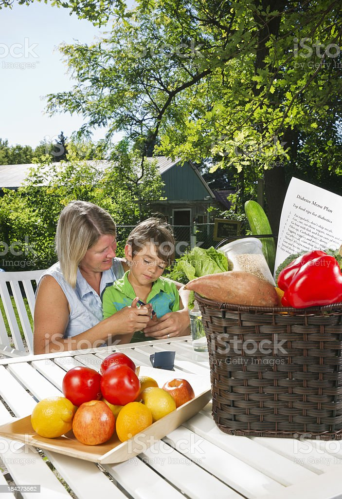 Mother helping her diabetic son take a blood sugar test royalty-free stock photo