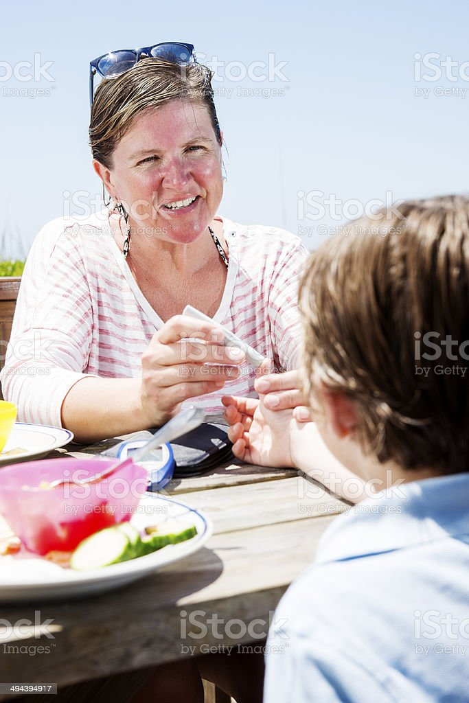 Mother helping her diabetic son test his blood sugar royalty-free stock photo