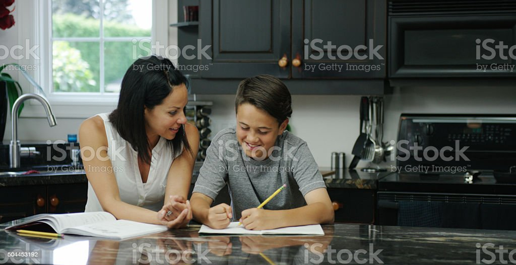 Mother Helping her Son with a Homeschooling Assignment stock photo