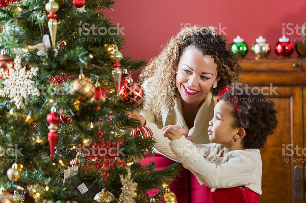 Mother helping little girl decorate Christmas tree stock photo