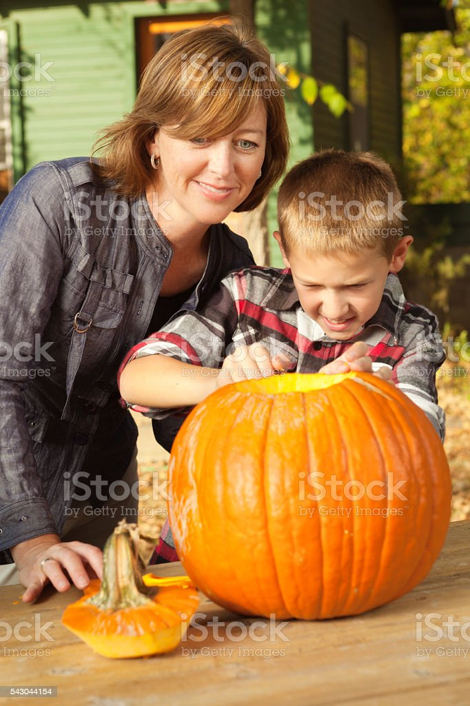 Mother Helping Son Carving Pumpkin for Halloween Festival stock photo