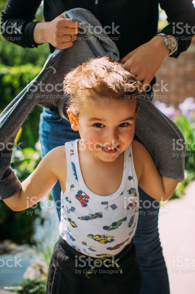 Mother helping son to undress stock photo