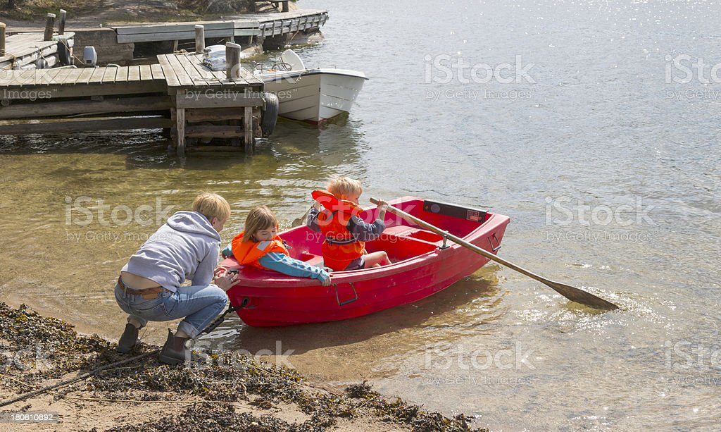 Mother helping two little children launch their red rowing boat. royalty-free stock photo