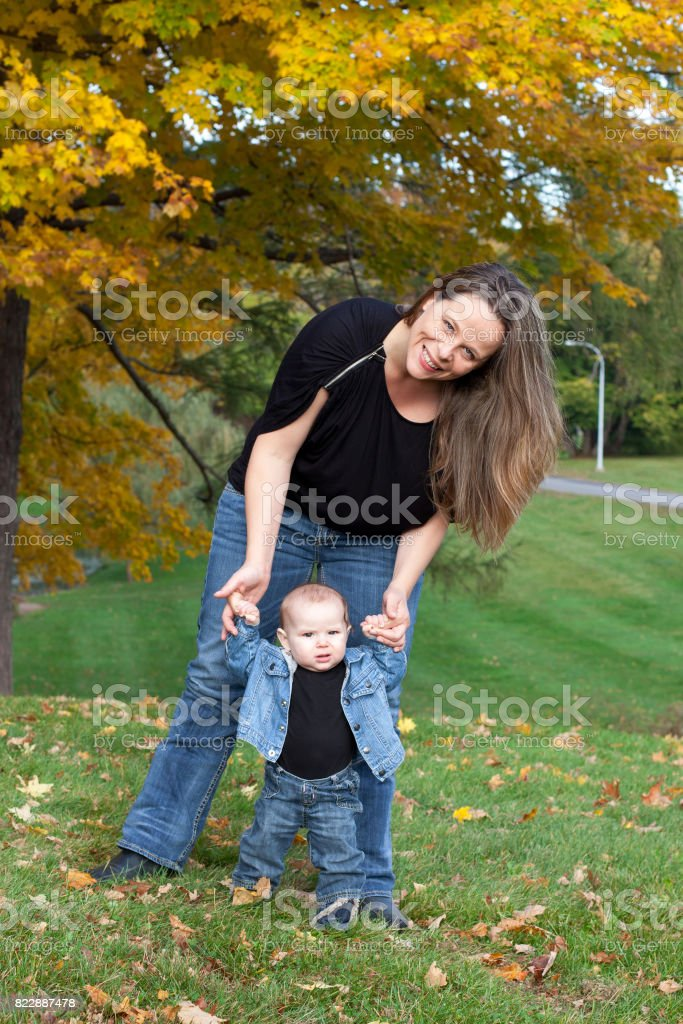 mother helps baby to walk stock photo