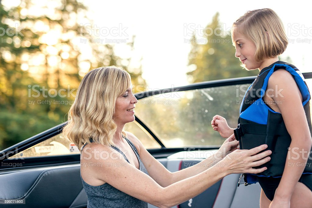 Mother helps daughter buckle her lifejacket stock photo