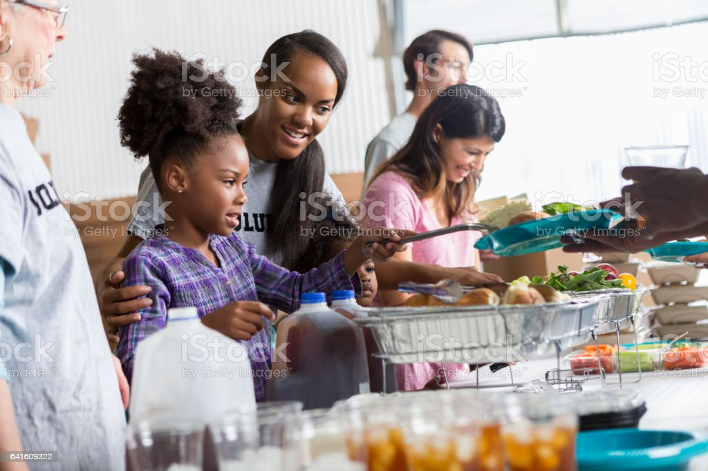 Mother helps daughter serve food in soup kitchen stock photo