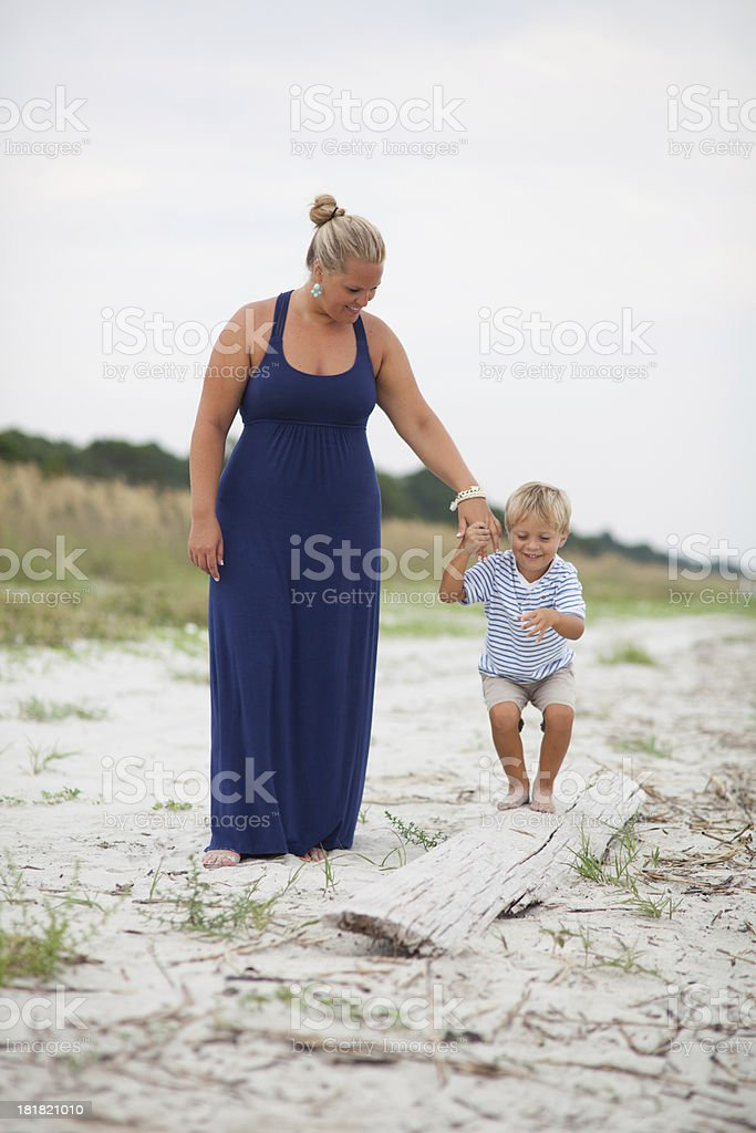 Mother helps young boy balance on log royalty-free stock photo