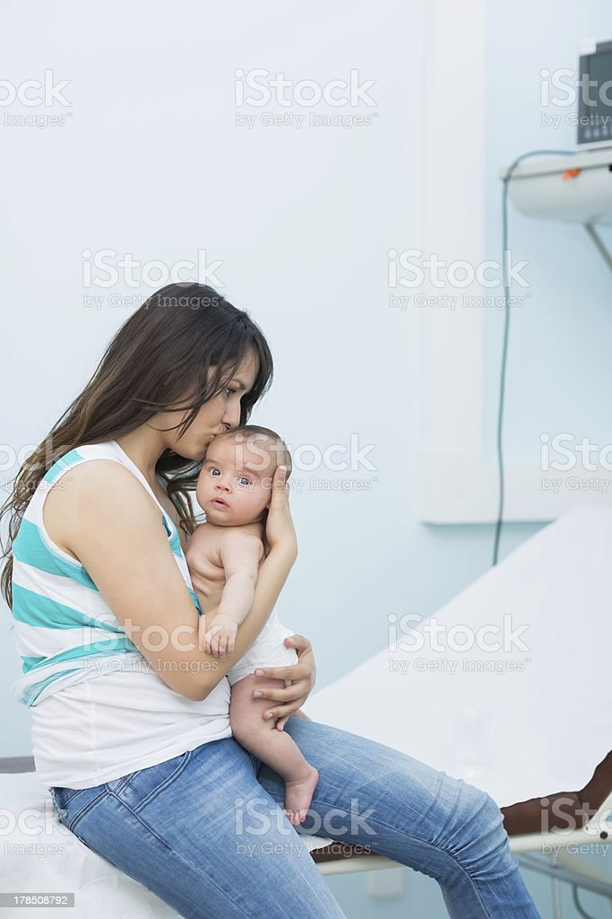 Mother holding a baby in an examination room royalty-free stock photo
