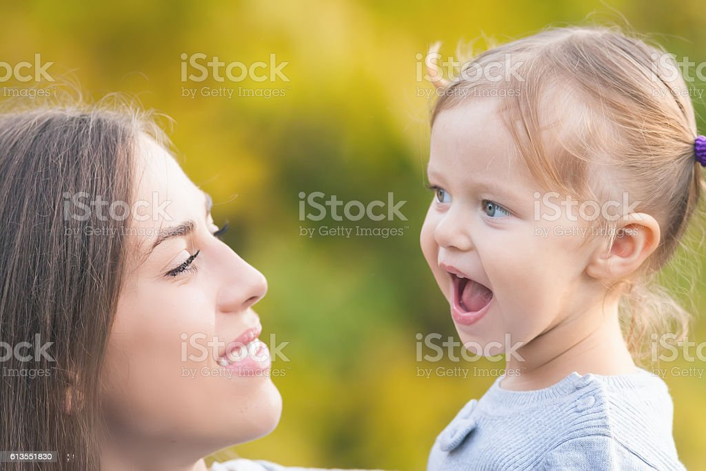 Mother holding a funny child outdoor. Fall colors background stock photo