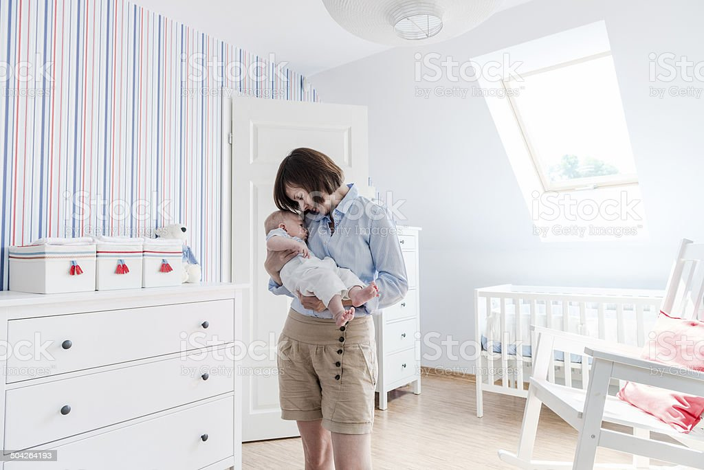 Mother holding and cuddling little baby boy tenderly, baby's room stock photo