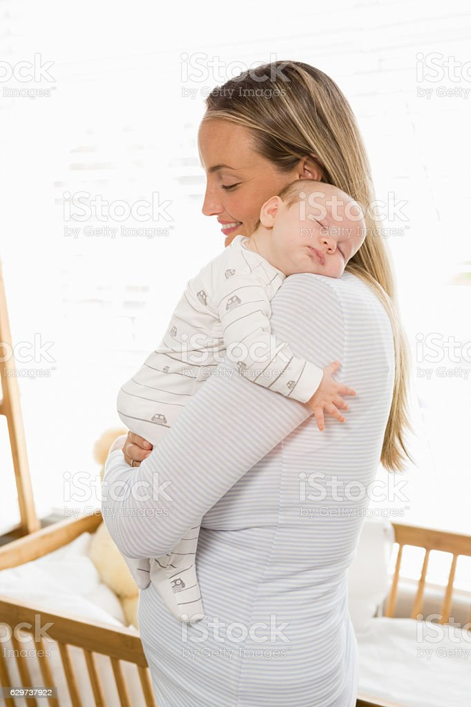 Mother holding and embracing her baby boy stock photo