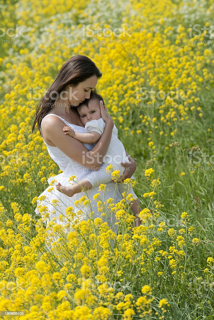 mother holding baby girl in flower field royalty-free stock photo