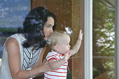 Mother holding baby girl (9-12 months) to window