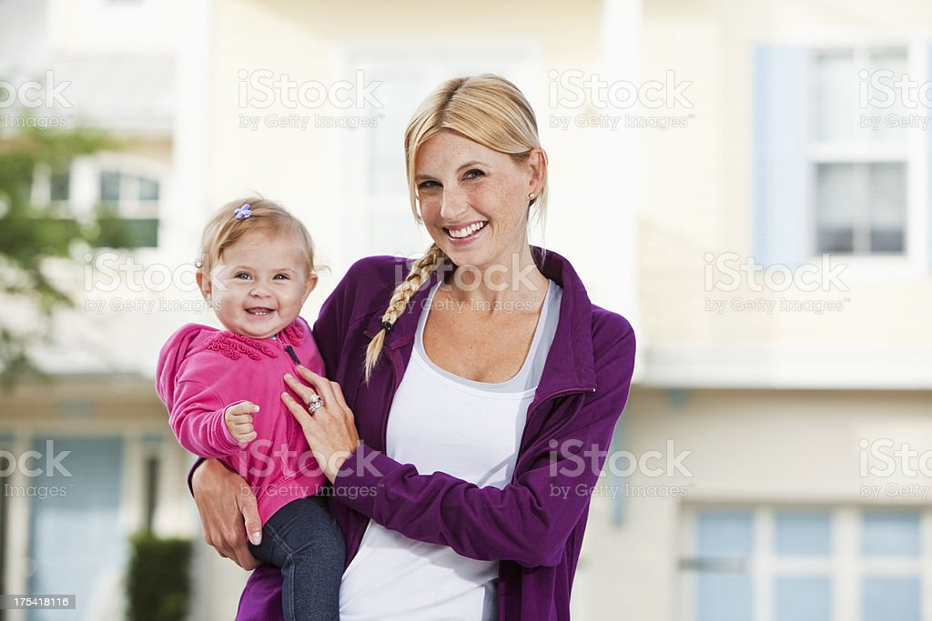 Mother holding baby in front of house stock photo